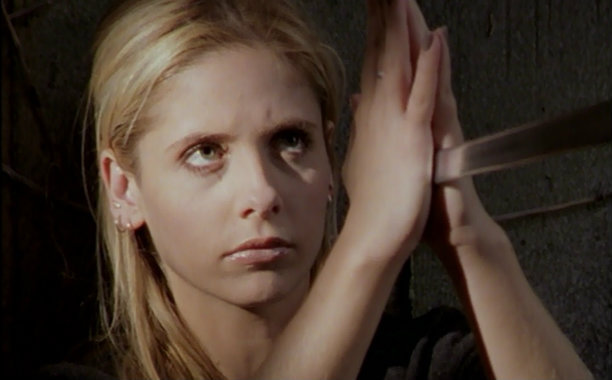Buffy fighting holding blade of a sword