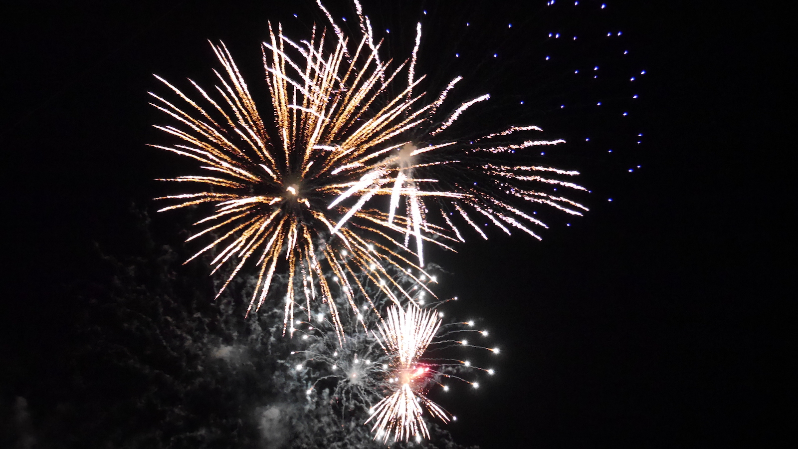Large fireworks on a night sky; lots of white sprays in different directions, with some yellow and some red. Also some smoke and blue sparks.